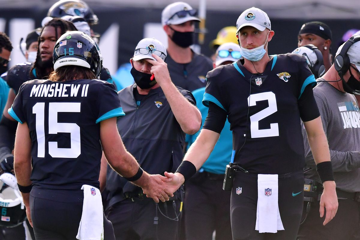 Gardner Minshew #15 of the Jacksonville Jaguars and Mike Glennon #2 shake hands on the sideline during the game against the Tennessee Titans at TIAA Bank Field on December 13, 2020 in Jacksonville, Florida.