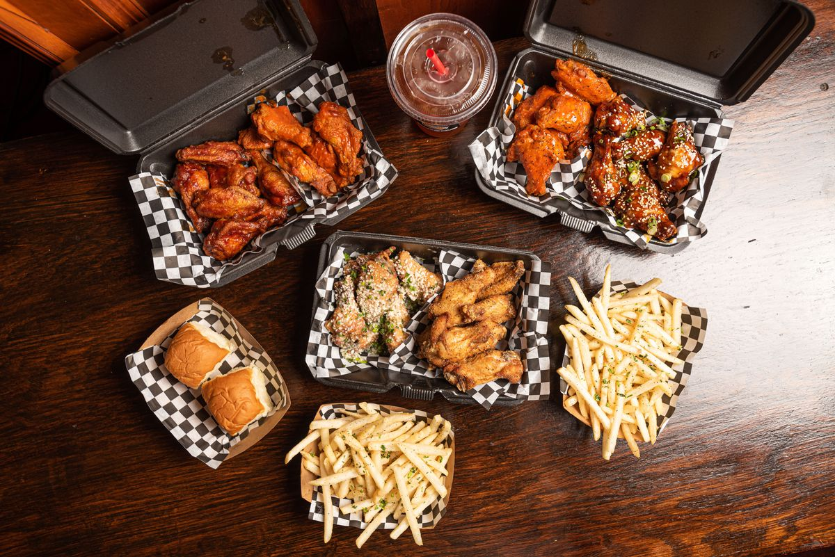 An overhead shot of a table with multiple wings and fry baskets.