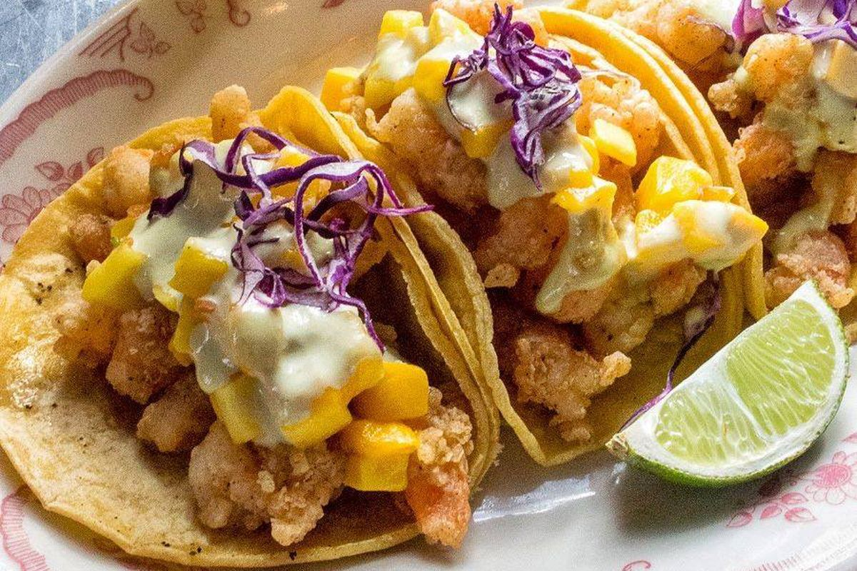 Three fish tacos with a beer