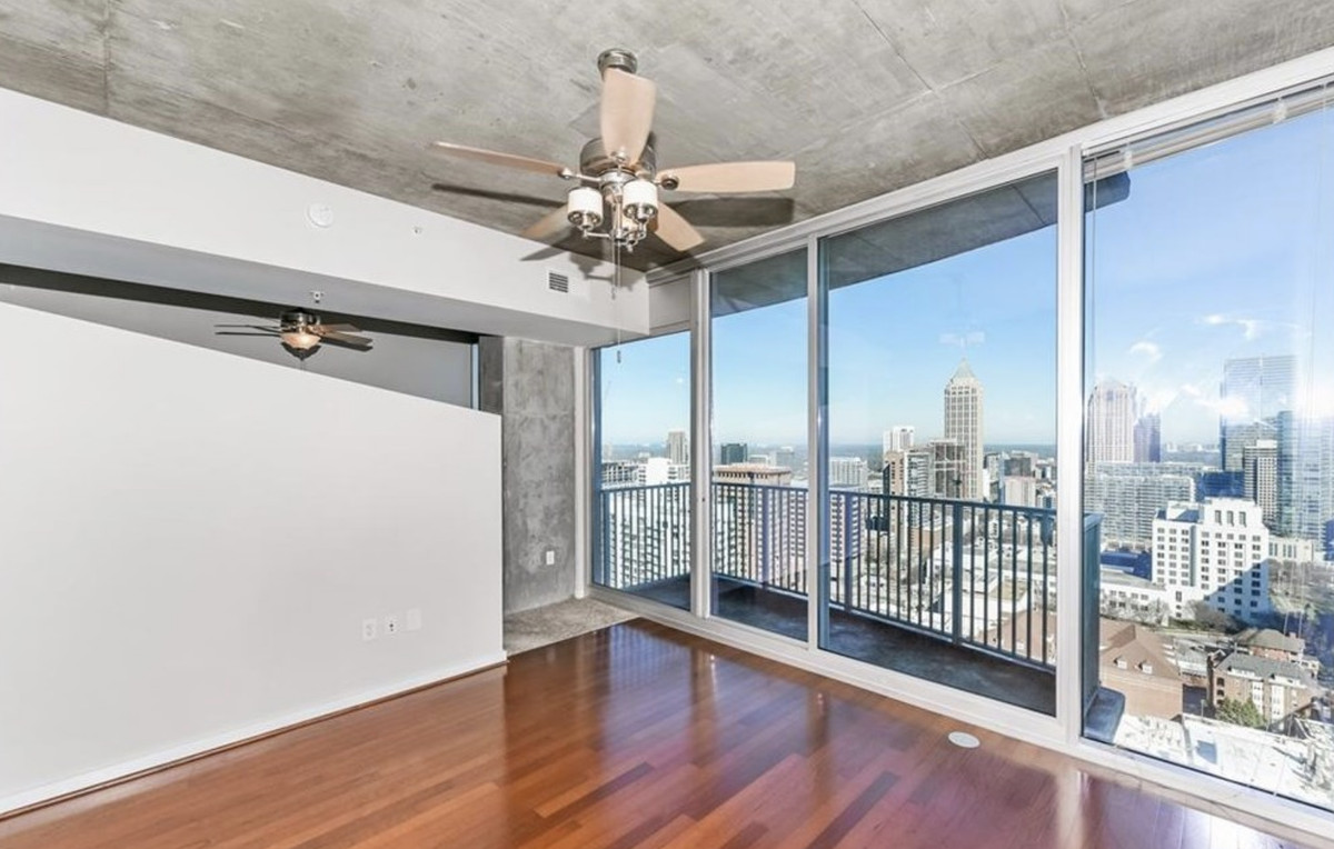 Empty room with hardwood floors and floor-to-ceiling windows overlooking the city.