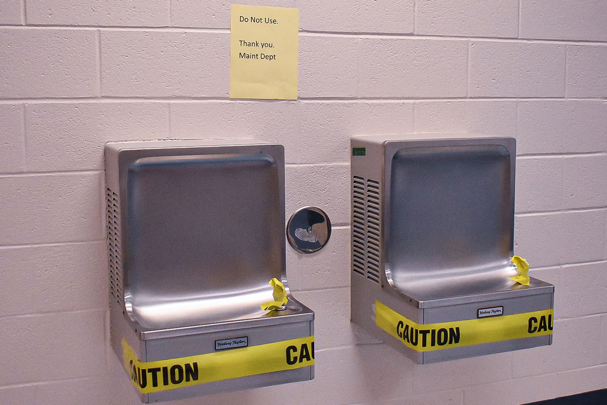 Two wall mounted water fountains are marked with tape to prevent their use.