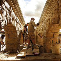 Doug Henriksen, at front, sprays cement on foam blocks at the Pontius Pilate's Court set.