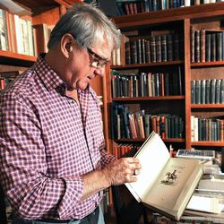 In this Aug. 10, 2012 photo, Thomas Minckler holds a copy of a rare Charles M. Russell book in Billings, Mont.  Minckler owns some of Montana's earliest historic documents.