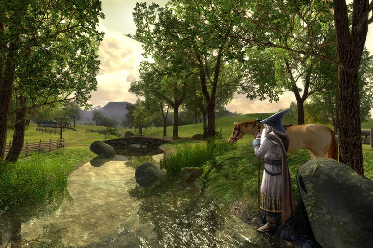 In this screenshot from The Lord of the Rings Online, a wizard in long gray robes and a pointy hat stands next to a horse in front of a small river. In the background, trees dot the landscape and a bridge runs across the river.