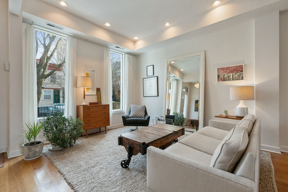 A formal living room with large windows, a couch, a wood table, and a large mirror.