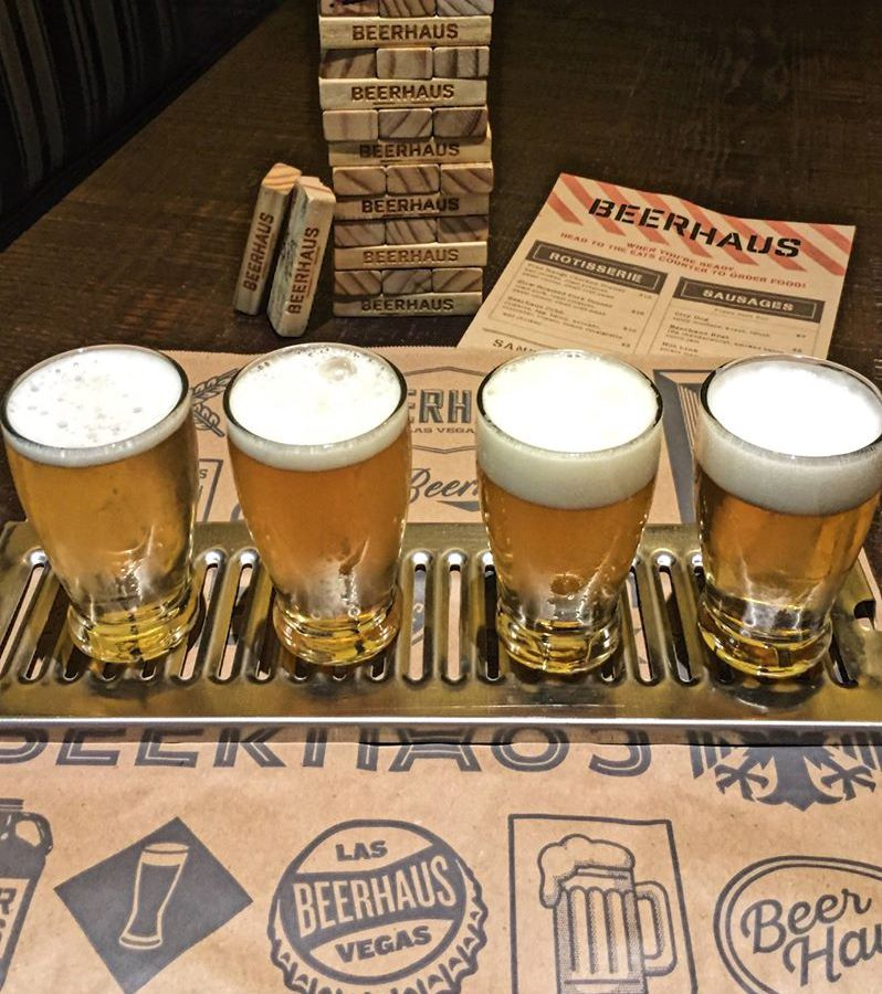 Flight of four beers with a menu in the background