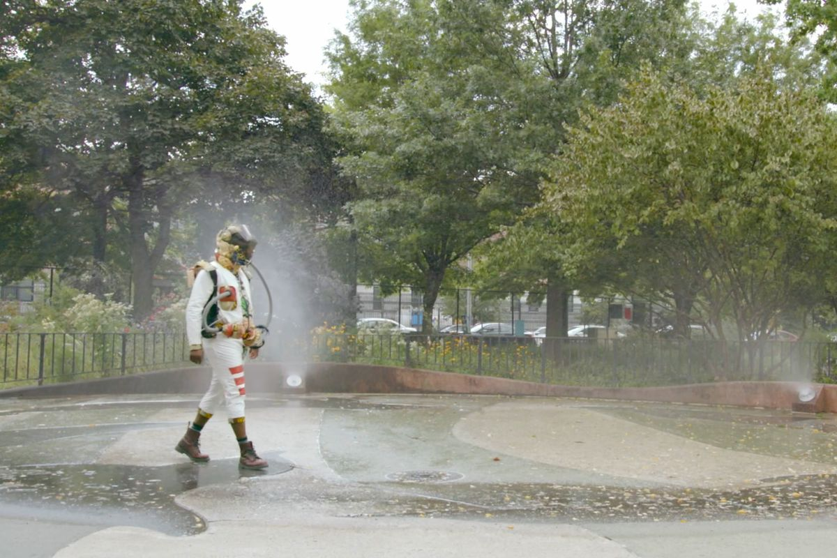 A person in a hazard suit and breathing gear, walking through a park.