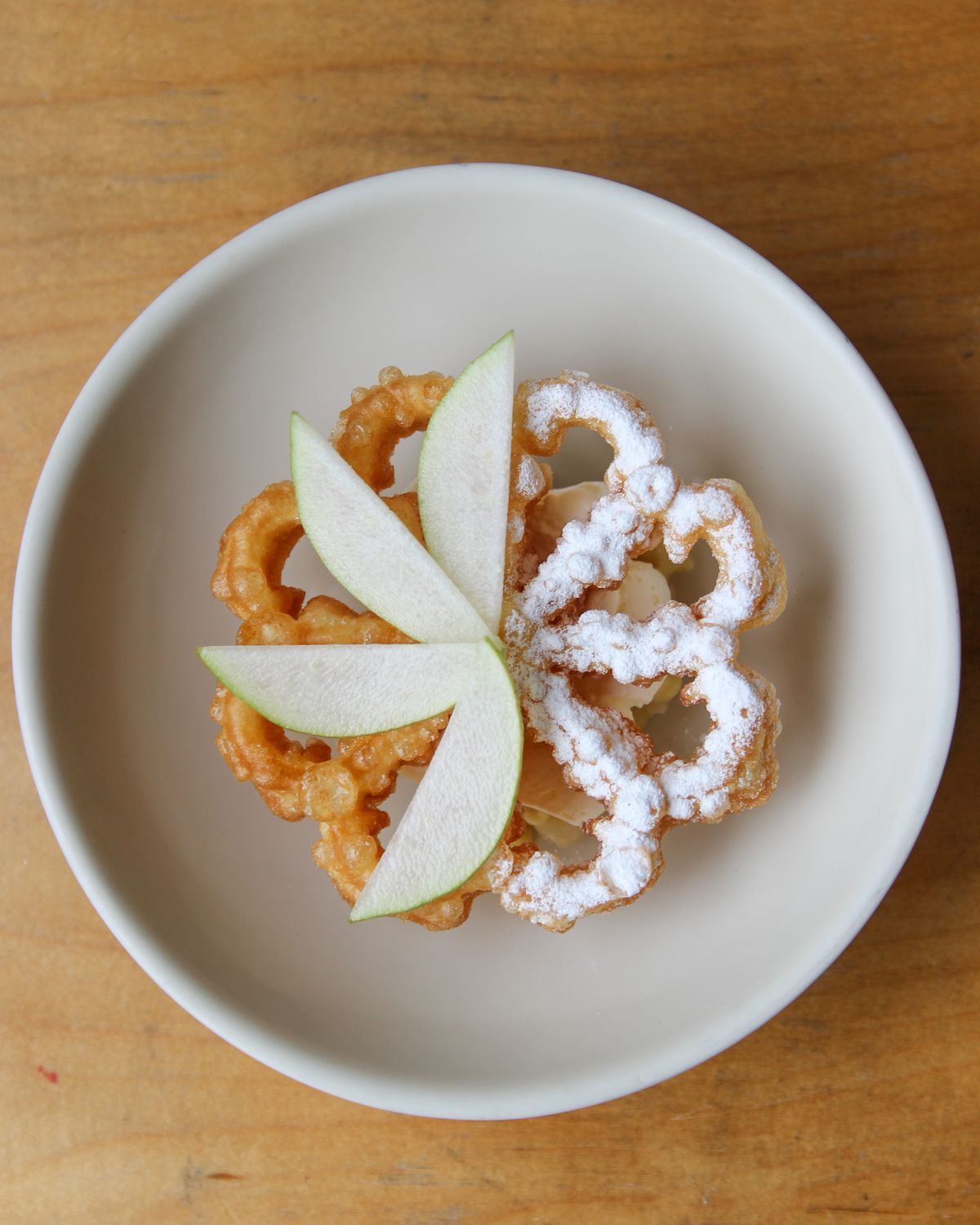 A fried piece of dough topped with slices of pears and some icing sugar