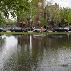 A man runs past a flooded field at Humboldt Park, Monday, May 18, 2020. Much of the Chicago area experienced flooding after rain showers over the weekend.