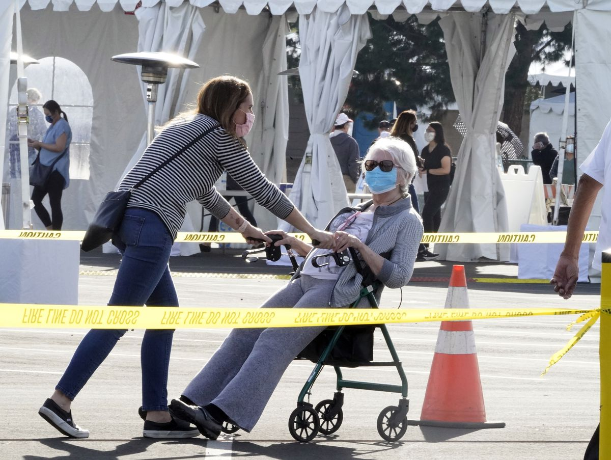 People walk after receiving their vaccines at the Disneyland Resort, serving as a Super POD (Point of Dispensing) COVID-19 mass vaccination site in Anaheim, Calif., Wednesday, Jan. 13, 2021.