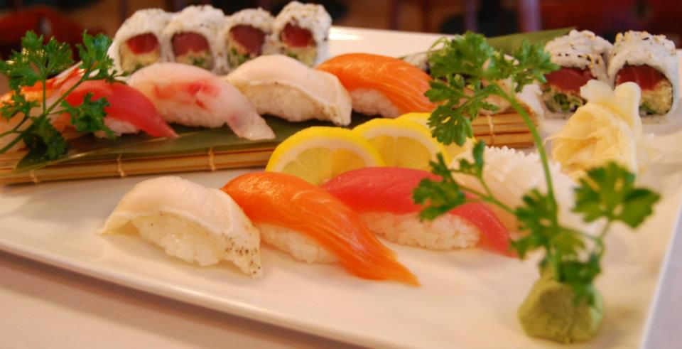 A plate of sushi, including pieces of salmon, a roll, and more