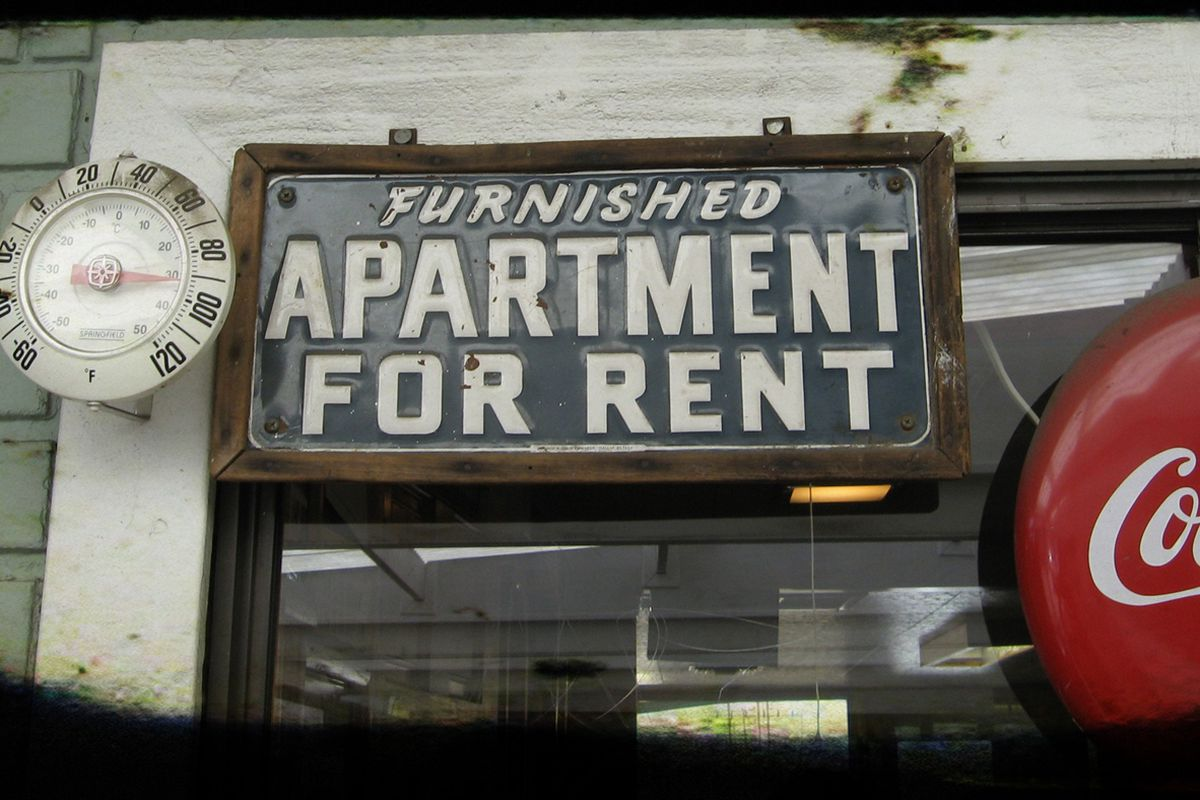 A tin sign that says Furnished Apartment for Rent between an old clock and a Coca-Cola sign