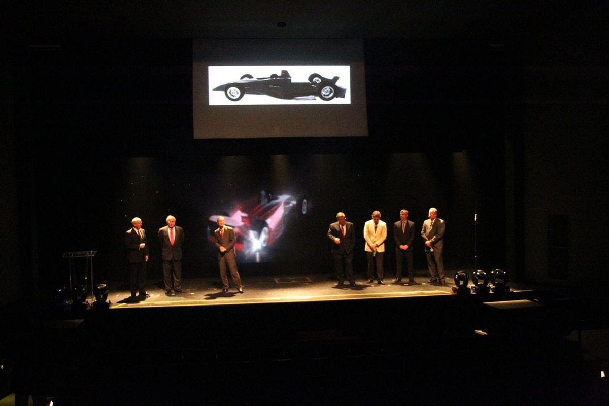 """The members of the IZOD IndyCar Series ICONIC advisory committee take the stage to announce the 2012 IndyCar chassis strategy. The Dallara-built """"Safety Cell"""" common tub is displayed in the background. (Photo: Ron McQueeney/IMS Photo)"""