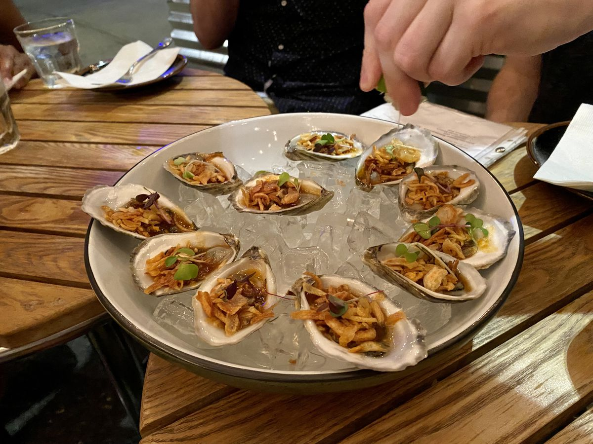 A hand squeezes lime juice into a tray of a dozen oysters loaded with chiles and other spices.
