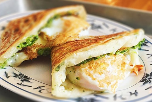 Eggs and greens are nestled in two folded scallion pancakes
