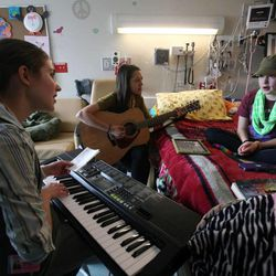 Music Therapy Intern McKenna Ence, left, and Music Therapist Amanda Maestro-Scherer play music with Sarah Magera, 13, who has AML leukemia, in her room at Primary Children's Medical Center in Salt Lake City on Thursday, Jan. 31, 2013.