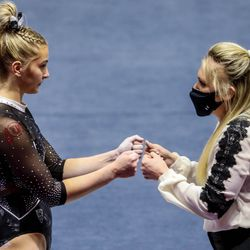 Utah's Lucy Stanhope, left, gets a pep talk as Utah and UCLA compete in a gymnastics meet at the Huntsman Center in Salt Lake City on Friday, Feb. 19, 2021.