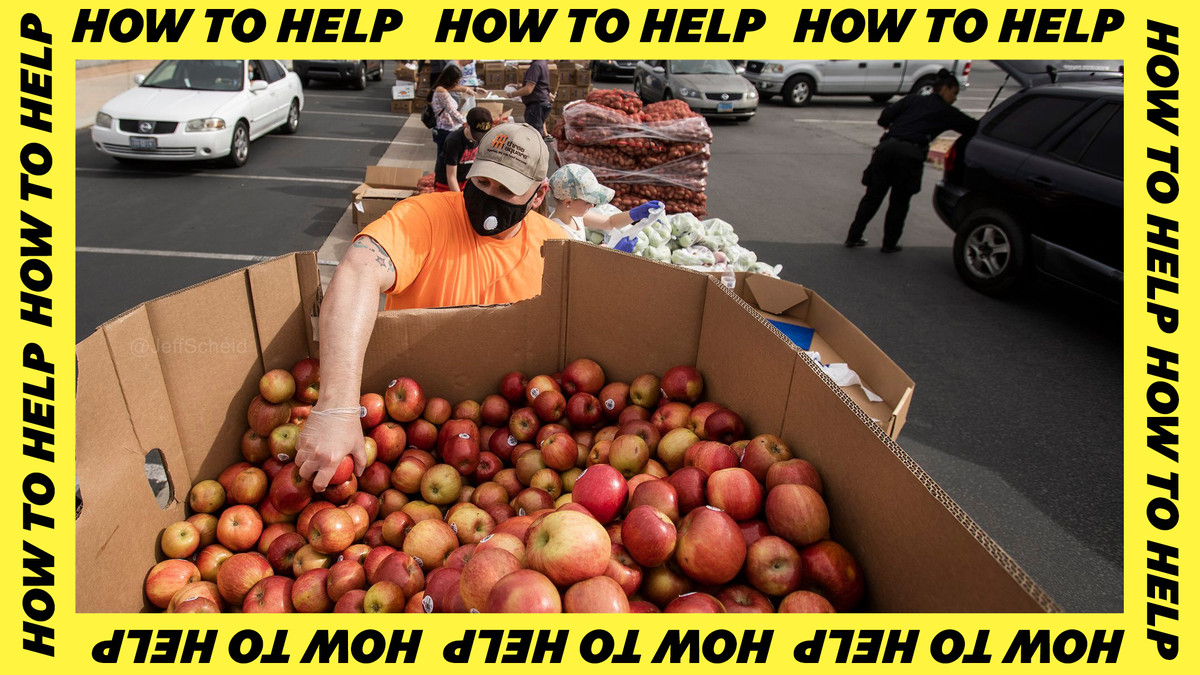 A man in an orange T-shirt grabs an apple from a box