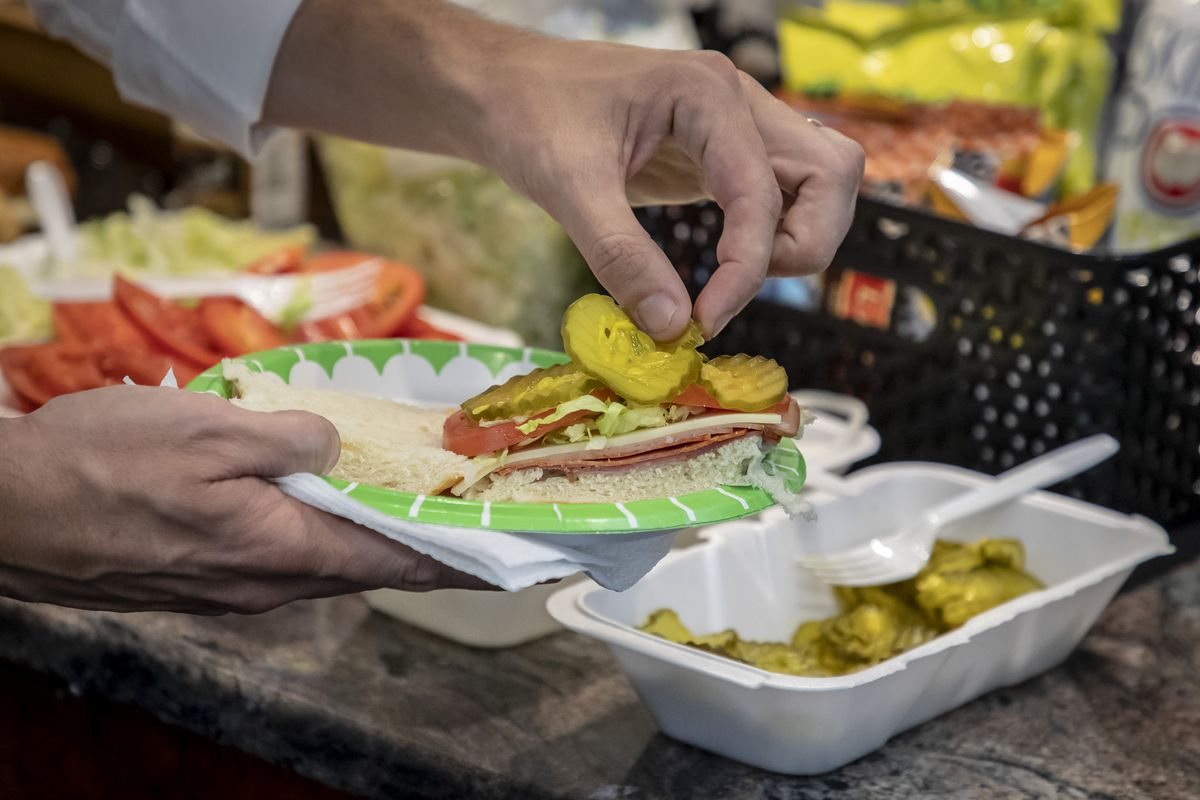 A hand placing pickles on an Italian sub.