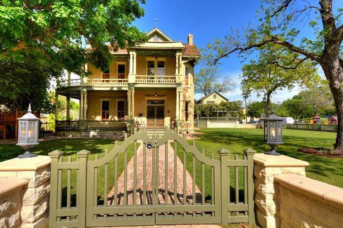 2-story yellow Queen Anne ish house with wraparound porch and veranda