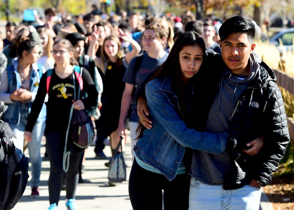 Rayne Macias, of Fairview High, and Jason Segovia, hug as they walk down the street with protesting Boulder High students. (Cliff Grassmick, Boulder Daily Camera)