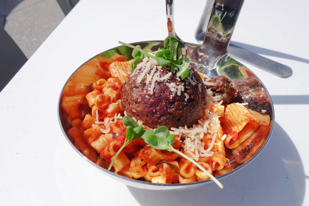 A meatball sits on top of pasta in a large metal spoon.
