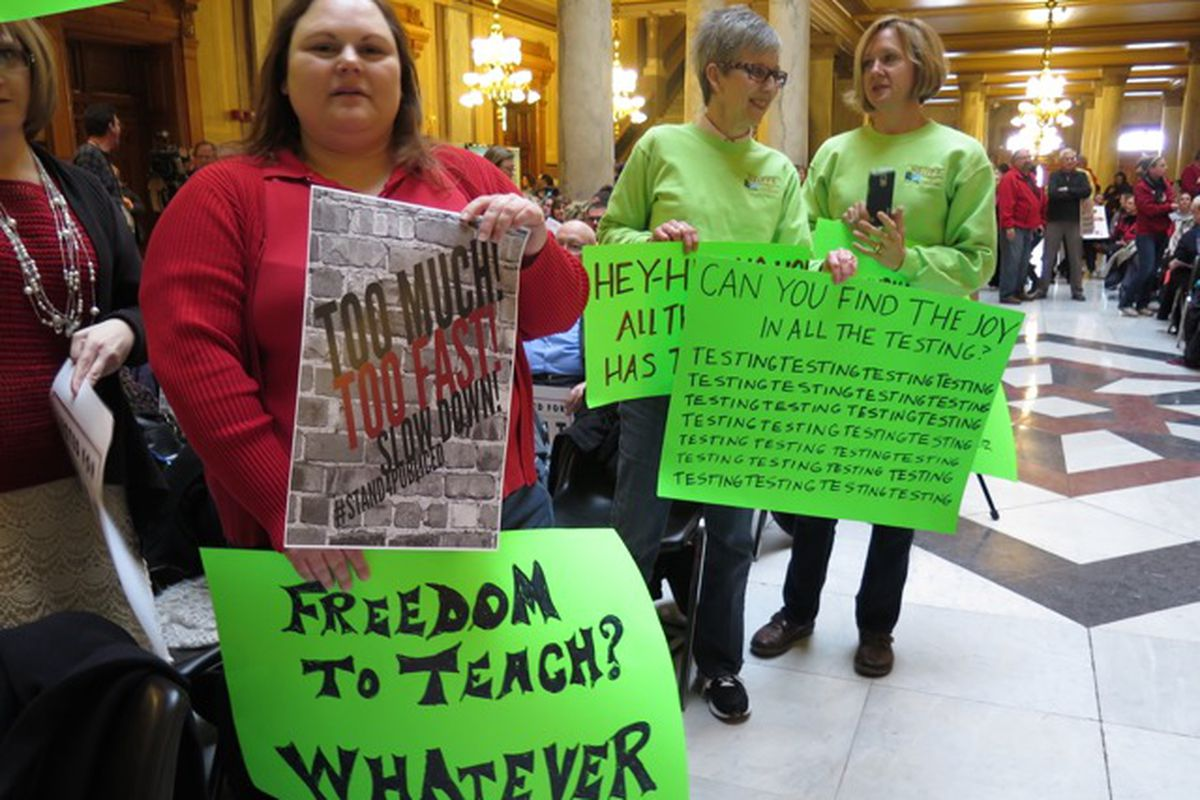Protesters hold signs criticizing testing and other concerns at a union-led rally at the statehouse last February.