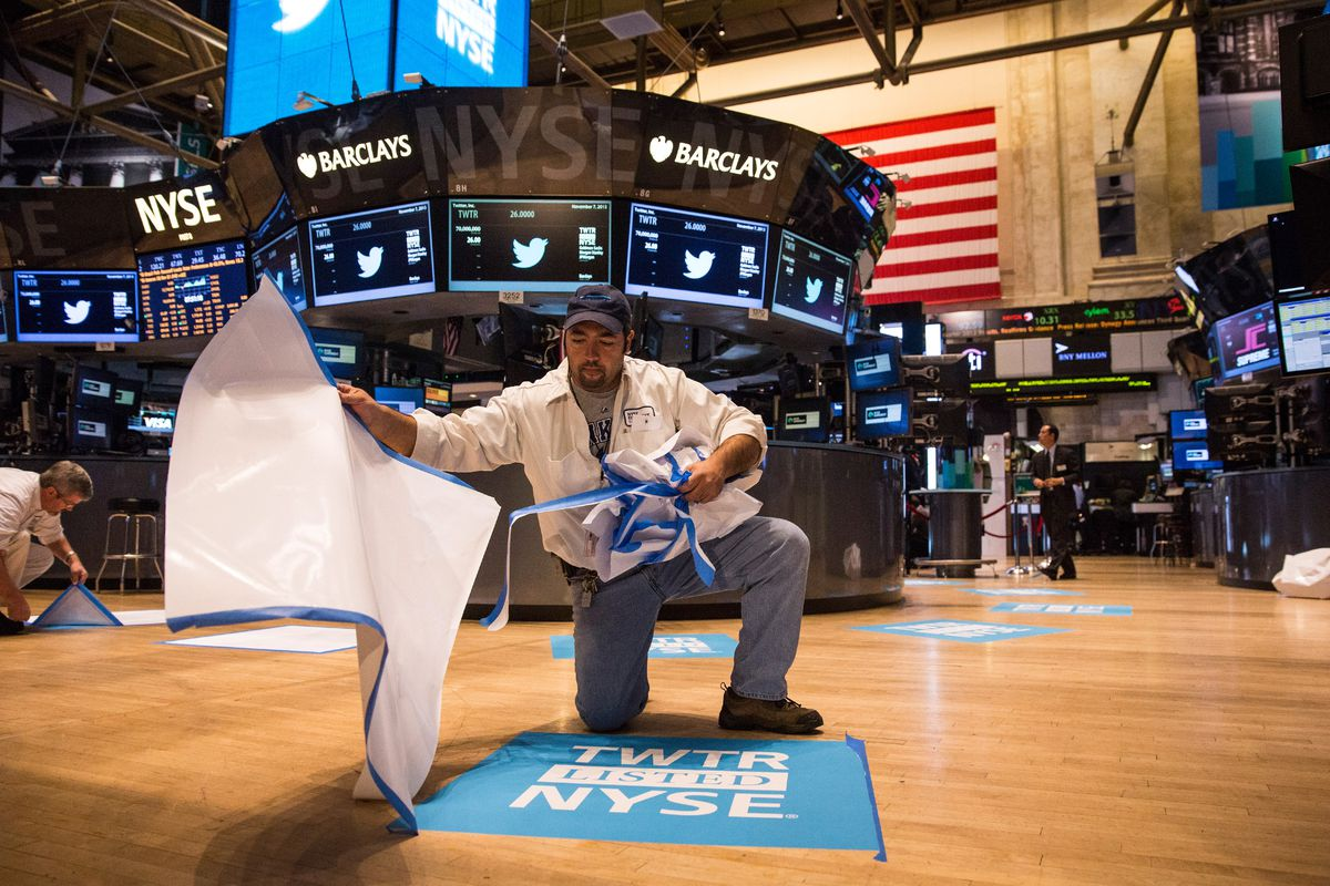 A worker peels the paper from a floor decal inside the New York Stock Exchange on the day Twitter stock debuted.