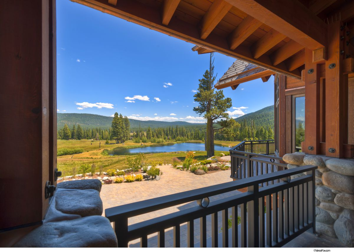 A view from a covered patio of the home out to an alpine pond.