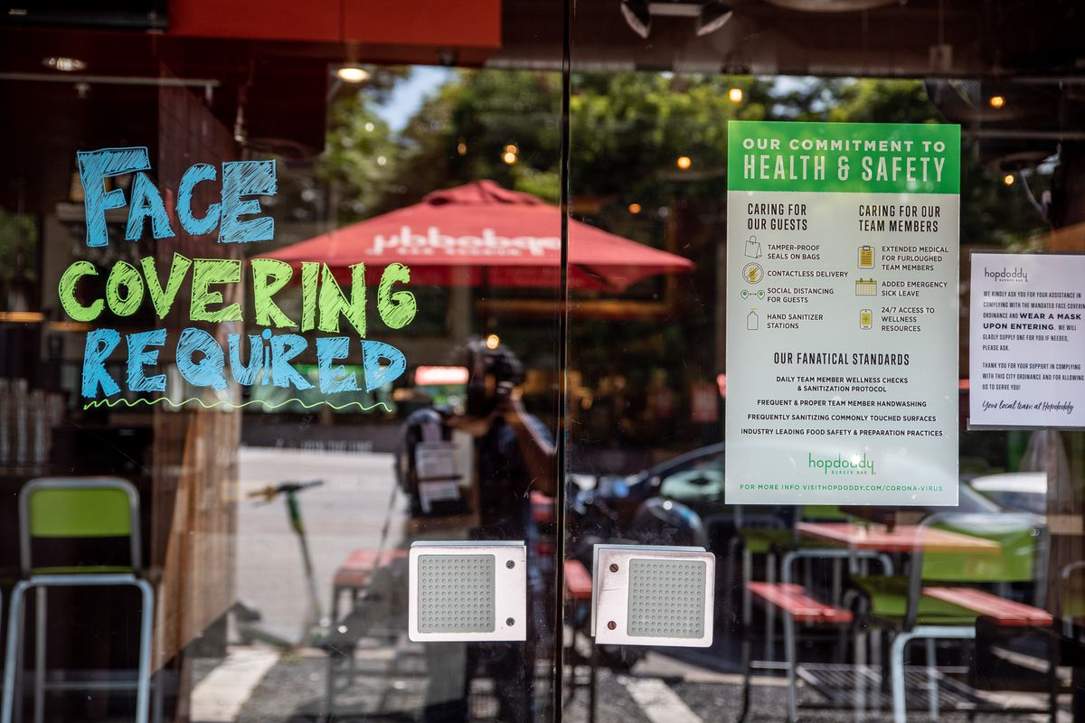 """A sign scribbled in bold blue and green marker declaring """"Face Covering Required"""" and green and white signage noting """"Our Commitment to Health and Safety,"""" listing out safety measures with icons, on top of a reflective restaurant window"""