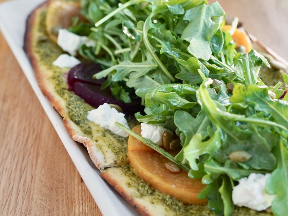 True Food Kitchen's fall flatbread with cilantro pumpkin seed pesto, red and golden beets, arugula, and goat cheese