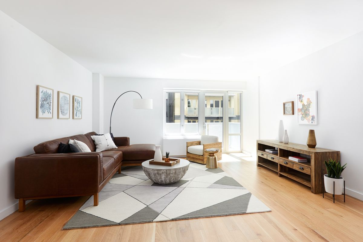 A living area with hardwood floors, a leather couch, a grey rug, a round coffee table, and large windows.