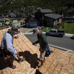 Brothers Carlos Aquiolar, left, and Rene Aguiolar, right, work on building a zero energy ready home in the Treseder at Little Cottonwood development in Sandy on Friday, Aug. 12, 2016. The development's model home, pictured in background, is featured in the Parade of Homes.