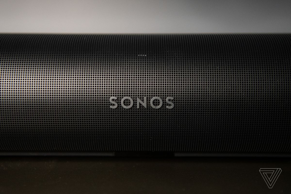 A aspect shot of the front of the Sonos Arc, showing the Sonos logo and a lot perforated holes within the outer casing.