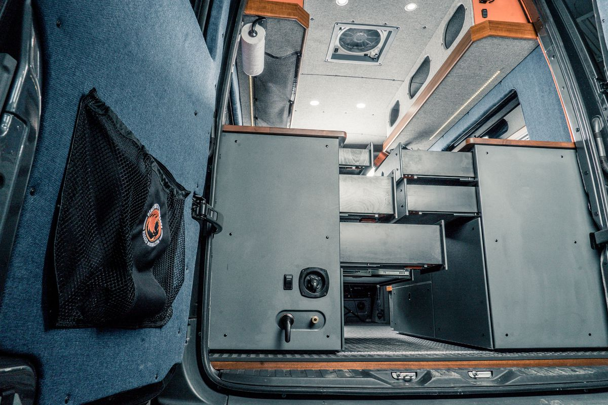 The interior of a camper van with counters that have many drawers and storage.