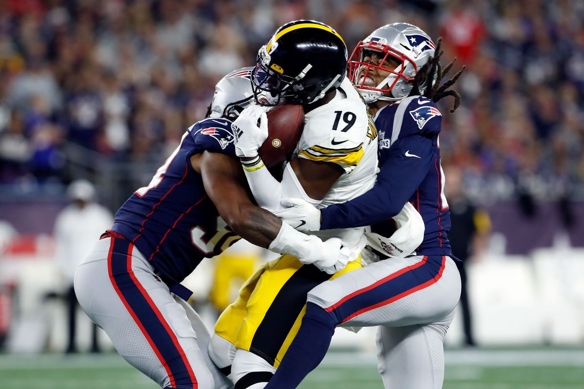 Pittsburgh Steelers wide receiver JuJu Smith-Schuster controls the ball while being tackled by New England Patriots outside linebacker Dont'a Hightower and cornerback Stephon Gilmore during the first half at Gillette Stadium.