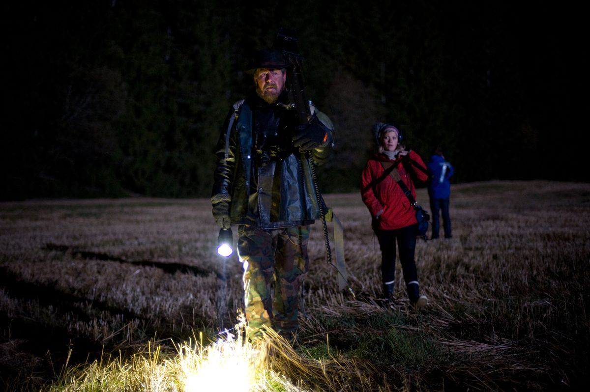 Three figures stand in a dark field, wearing backpacks and wielding flashlights.