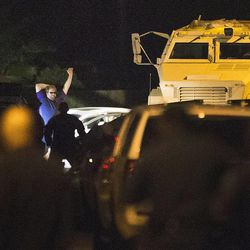 Law enforcement officers surround a shooting suspect Wednesday, July 9, 2014, in Spring, Texas. After hours of waiting and negotiations, the man, suspect in the slayings of six people, including four children, emerged from his car, raised his hands and sank to his knees as deputies placed him under arrest. No identity has been released. (AP Photo/Houston Chronicle, Brett Coomer)