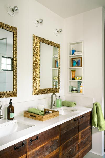 Double bathroom vanity with wooden cupboards and golden mirrors above sinks.