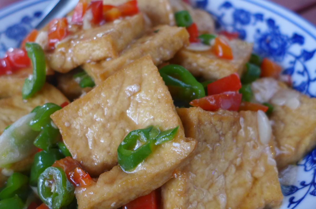 A blue plate of bean curd squares dotted with green chiles.
