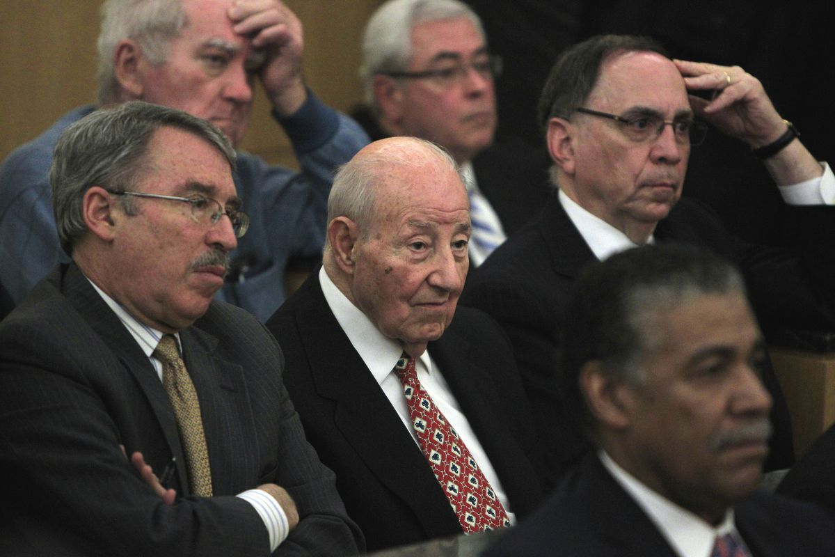 Several people in black suits sitting in rows. Two have their hands on their forehead in dismay.