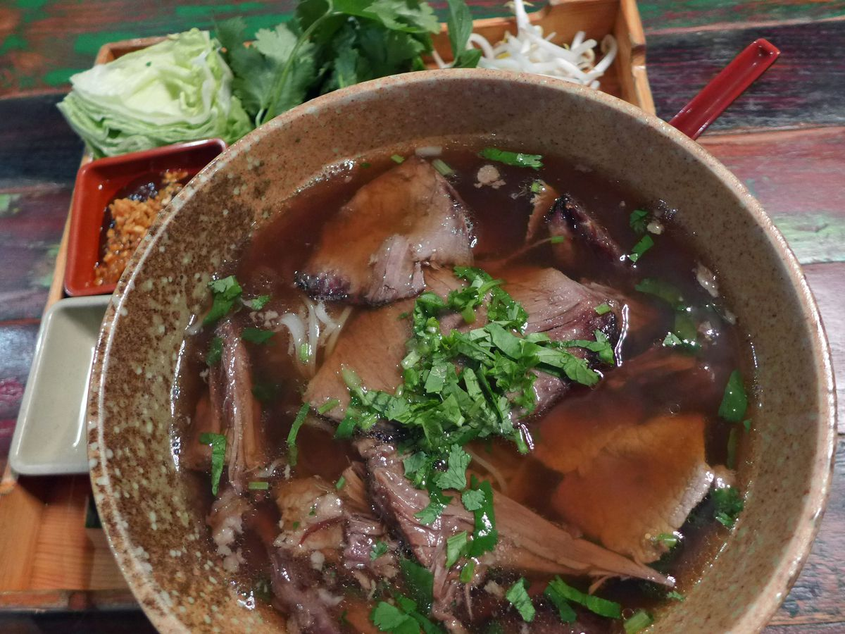 A stoneware bowl of pho with a dark broth and slices of beef floating on top.