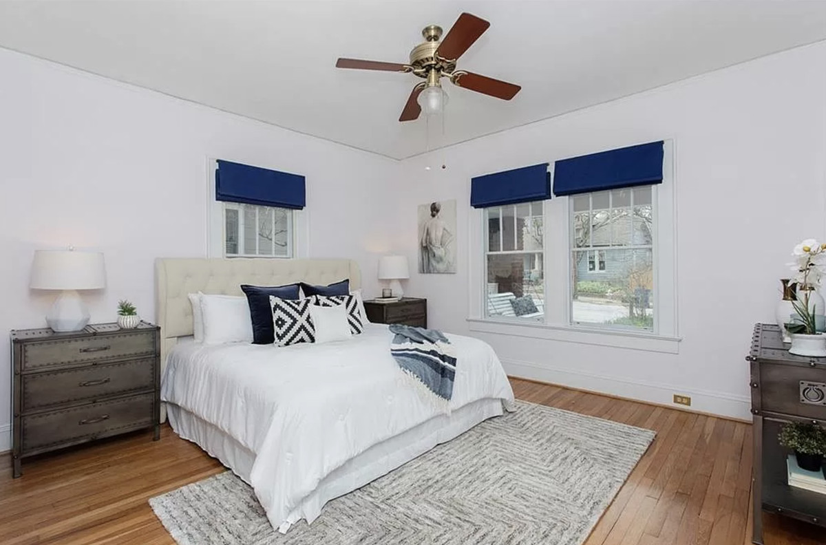 Bedroom with bed, nightstands with lamps, area rug, and windows with blue window treatments.