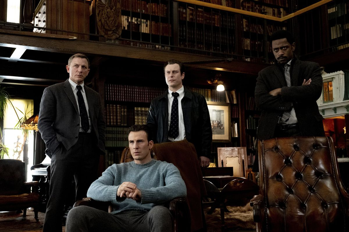 A seated Ransom (Chris Evans), surrounded by Blanc (Craig) and the police.