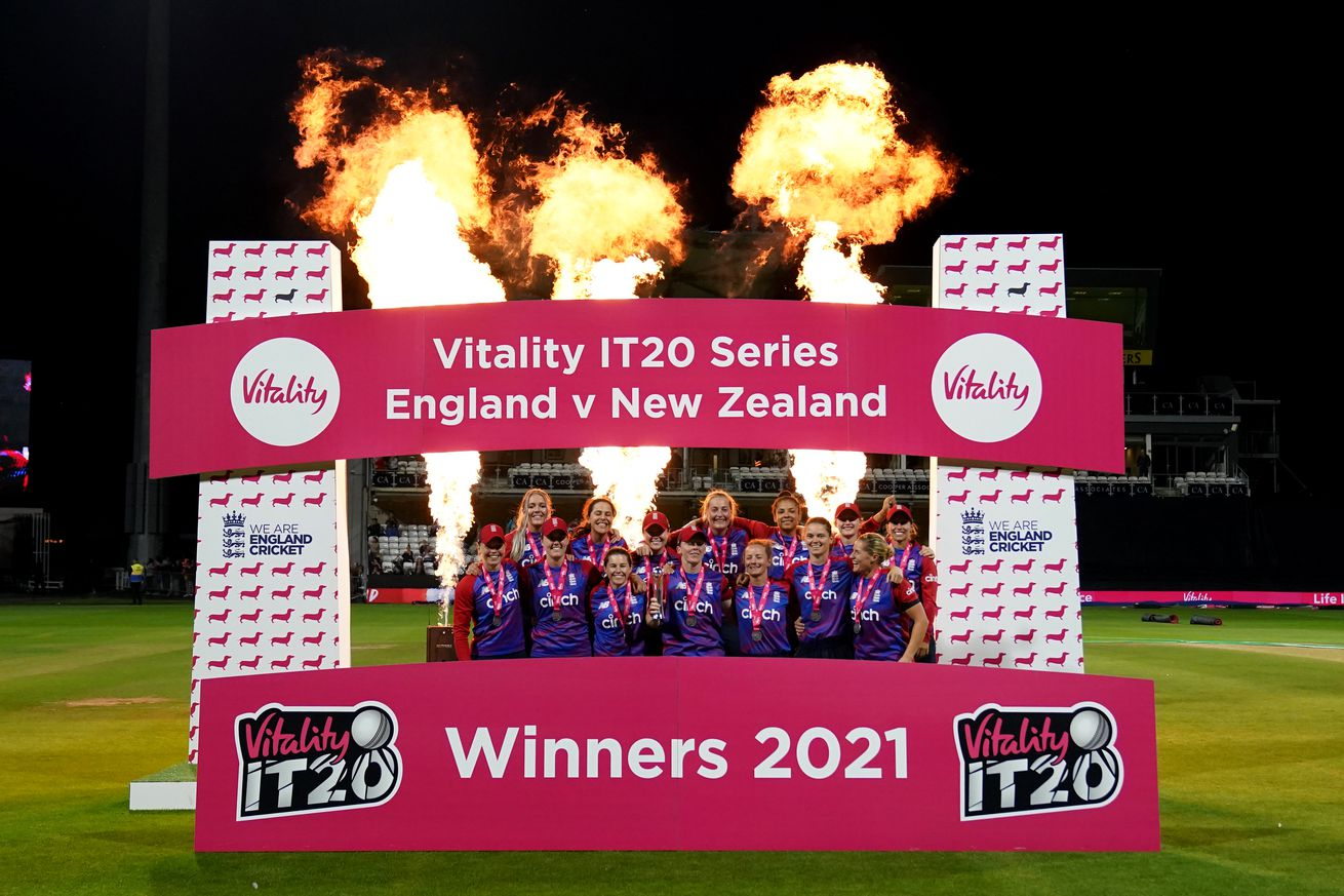 The English woman's cricket team poses with a trophy behind a red and white facade with three very large pillars of fire spraying into the air behind them