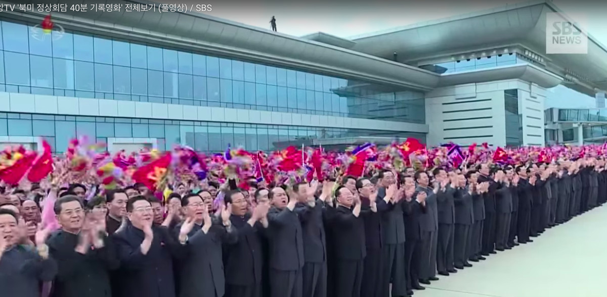 Hundreds of North Korean party officials cheer and wave small North Korean flags at Pyongyang airport to welcome Kim Jong Un back home after the summit.