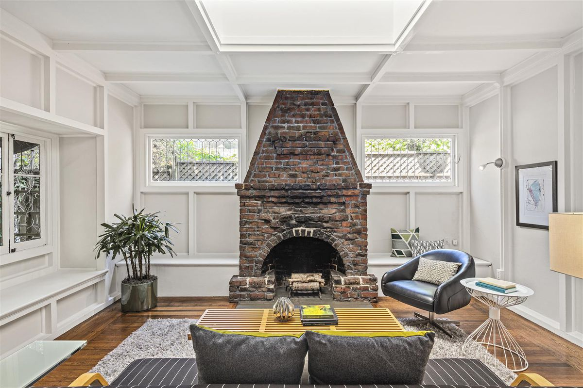 A red brick fireplace aged with black marks sits at the end of a living room with beams painted white.