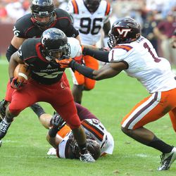 Cincinnati running back George Winn has his face mask grabbed by Virginia Tech cornerback Antone Exum (1) during the first half of an NCAA college football game, Saturday, Sept. 29, 2012, in Landover, Md.