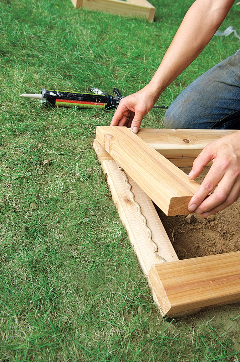 Man Applies Adhesive To Stack Planter Bench Base Boards On Top Of One Another
