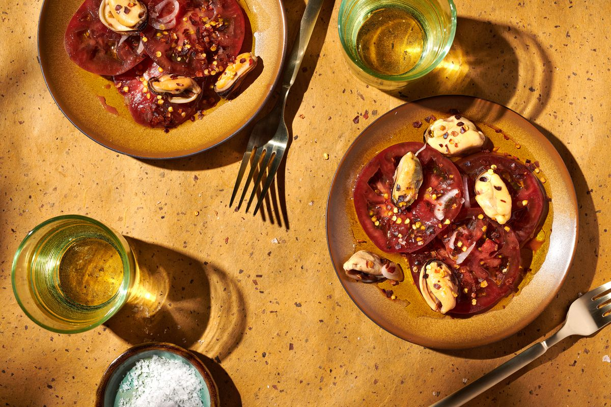 Two plates of marinated mussels and tomatoes sit on a table with forks and beverages.